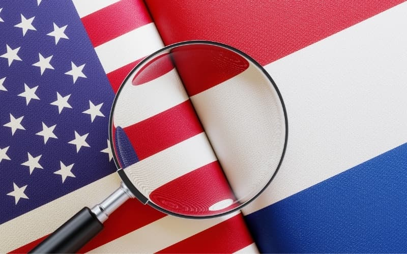 Dutch police vs American police - American And Dutch Flag Pair Under A Magnifier